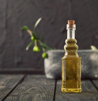 Olive oil on top of a wooden countertop.