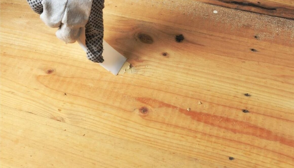 A woodworker applying wood putty on the floor.