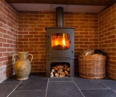 A freestanding wood stove installed in a fireplace.